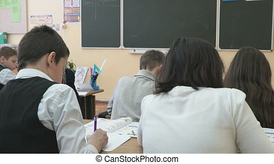 Students sit at school desks in a class at school