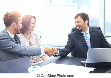 Business colleagues sitting at a table during a meeting with...