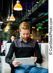 Redhair man with tablet - Young redhair man sitting in cafe...