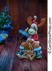Toy Christmas reindeer in Christmas clothes sitting on a wooden sledge