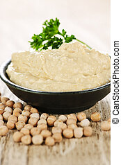 Hummus with chickpeas - Bowl of fresh hummus with raw...