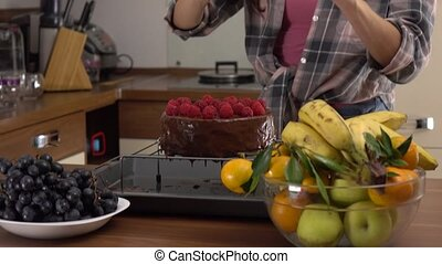 Brunette young woman making pictures of her chocolate and raspberry cake. Steadicam 4K video