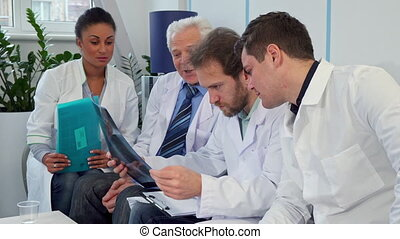 Medical team discusses x-ray image - Medical team discussing...