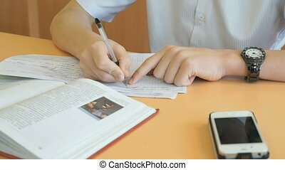 Teenager writes the text in a copybook on a lesson