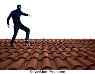 Thief on the roof - Thief dressed in black walking on the...