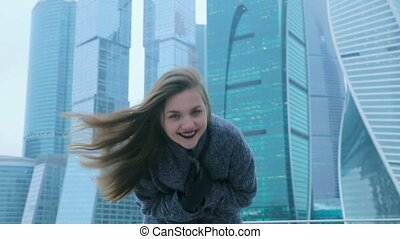Girl posing against the backdrop of a skyscraper