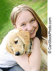 Girl with puppy - Portrait of smiling teenage girl holding...