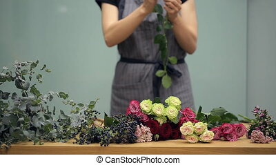 Florist prepares cut fresh flowers for a mixed bouquet arranging.