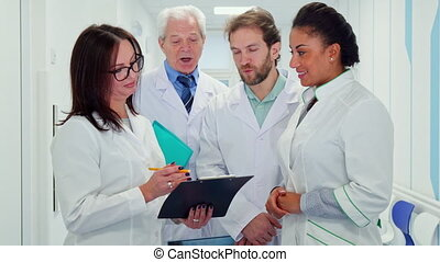 Medical team looks at clipboard - Multiracial medical team...