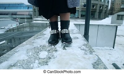 Girl dancing in boots in the snow.