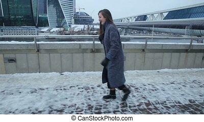 Girl in coat slide on snow