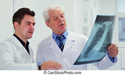 Two male doctors look at x-ray
