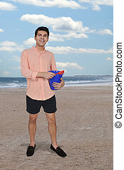 Man with a sand pail - Handsome young man holding a sand...