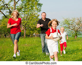 Family playing ballgames - Happy family playing football,...