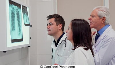 Medical team analizes x-ray on x-ray view box - Side view of...