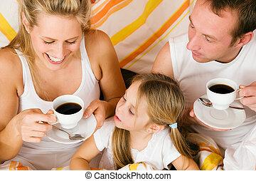 Family breakfasting in bed