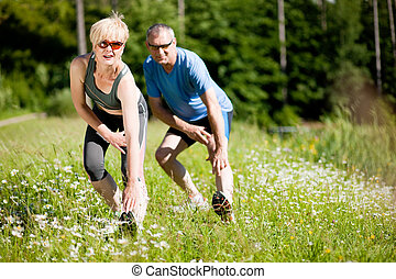Mature couple doing sport outdoors - Mature or senior couple...