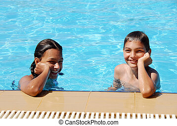 Smiling children in swimming pool - smiling girl and boy in...