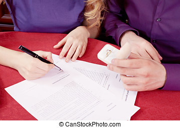 Prenuptial agreement signing - Close-up of woman signing a...