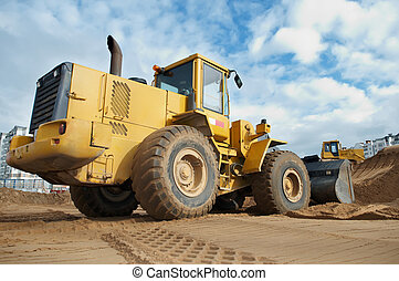 wheel loader at work - Wheel loader machine loading sand at...