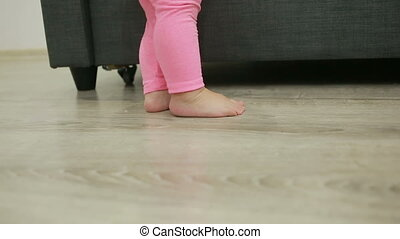 little girl walks barefoot in her living room,