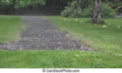 Heavy rain water drops falling on garden stone pavement and...