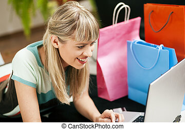 woman shopping online via Internet - Woman lying in her home...