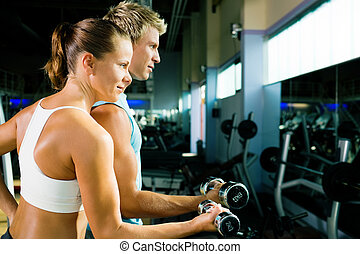 Lifting the dumbbells - couple in the gym, rivaling each...