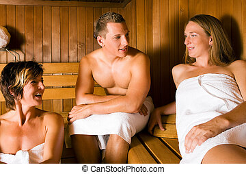 Friends in the sauna - Three people (one male, two female)...