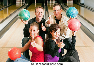 Friends bowling together - Group of four friends in a...