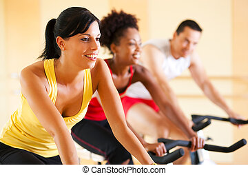 Bicycle Spinning in gym - Group of three people - presumably...