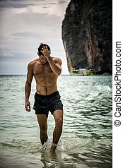 Young man standing on edge of the ocean - Half body shot of...