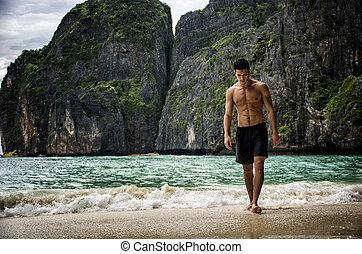 Young man standing on edge of the ocean - Full body shot of...