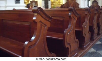 Old carved wooden benches in catholic church 4K steadicam...