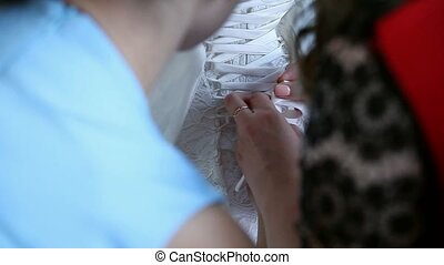bridesmaid makes bow-knot on the back of brides wedding...