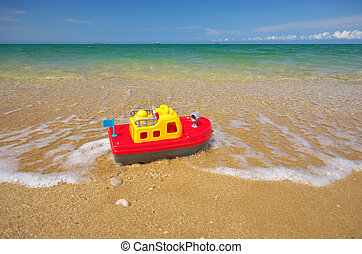 Toy ship on the sea shore. Nature and conceptual design.