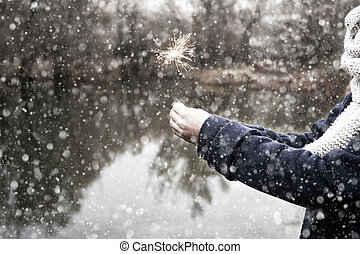 Woman holding sparkler in forest, winter snow day