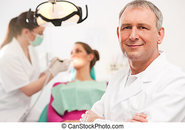 Dentist in his surgery looking at the viewer, in the...