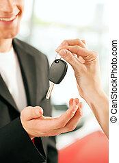 man buying car - key being given - Man at a car dealership...