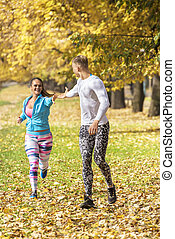 Beautiful young couple running together in the park. Man helps woman giving his hand. Autumn environment.