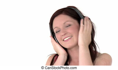 Charming girl listening to music against a white background...
