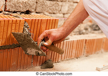 bricklayer making wall with brick - bricklayer laying, well,...
