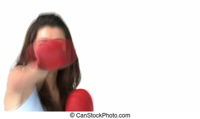 Confident asian woman with boxing gloves against white...