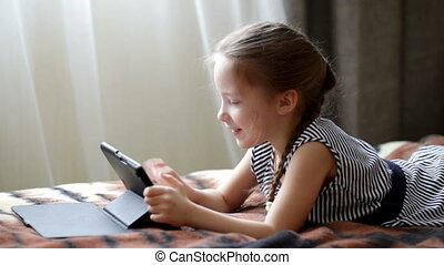 Cute little child girl playing in a tablet computer