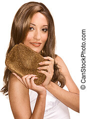 Portrait of young attractive Middle Eastern female in white dress in light brown shiny wig holding golden colored purse