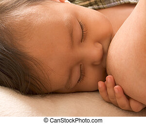 Sleepy baby boy enjoying breastfeeding - Infant holding his...