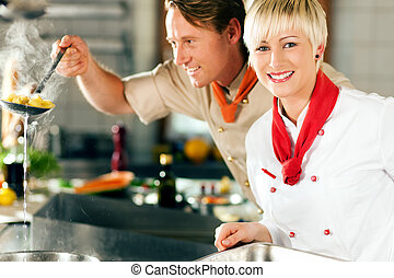 Chefs in a restaurant or hotel - Two chefs in teamwork - man...