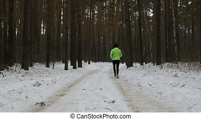male and female runner running on winter trail in woods,...