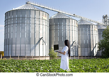 Agronomist with laptop with silos behind - Young woman...