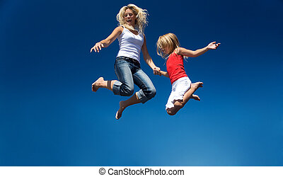Flying - A mother and her daughter jumping high having lots...